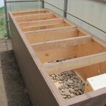 """Heat collected in SunnyTherm's solar panels is ducted into a """"rock-box"""" heat bank in Joanne Lederhos's high-altitude greenhouse. The stones store heat from the sun and release it after dark."""