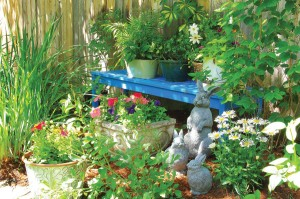 """The blue bench I painted myself when a friend suggested blue accents for our yard,"" Kristin says of the teak bench they found in the alley. The houseplants atop the bench summer outdoors and overwinter indoors. The bunny sculptures add ""variety and softness"" to the garden, Kristin says. ""I like the animals, and so do my grandchildren."" Photo by Allison M. Fleetwood Jr., wwwamfjphotography.com."