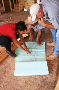 Kirsten Snobeck of Rodwin Architecture consults with the Skycastle Construction crew on a green design-build project. (Photo courtesy Rodwin Architecture)