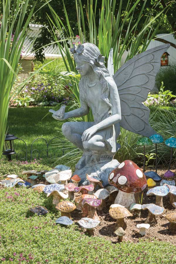 a large fairy keeps watch over a village of fairy houses and mushrooms many of which june crafted from clay in her studio photo by