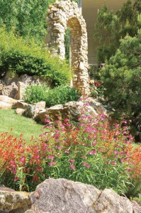 """Working with """"artscaper"""" Marco Viera, George Emmons and Scott Shevlin made their steep, rocky lot into a perfect place to garden, relax and entertain. The imposing stone arch—the focal point of the front yard—was added after a huge cottonwood fell and crushed its metal predecessor."""