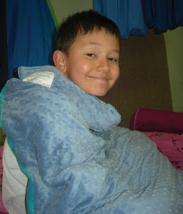 A weighted blanket applies deep pressure, akin to a hug, that comforts autistic children and also helps with sleep problems. (photo courtesy Autism Community Store)